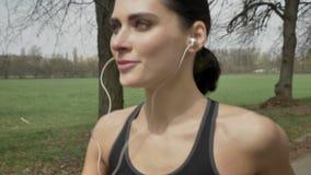 年轻愉快的体育女孩跑与耳机在公园在夏天,健康生活方式,体育构想,侧视图 影视素材