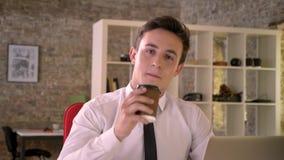 年轻愉快的商人在办公室喝在工作场所的咖啡,观看在照相机,企业概念,通信 股票视频