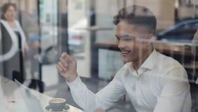 年轻愉快的商人谈话在电视电话会议与一台膝上型计算机的电话闲谈在咖啡馆 他笑和乐趣笑话与他的 影视素材