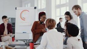 年轻愉快的在现代不同种族的健康办公室慢动作红色史诗的黑人妇女上司主导的队讨论会议 影视素材