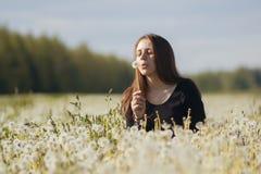 年轻愉快的在蒲公英的领域的妇女吹的蒲公英 库存图片