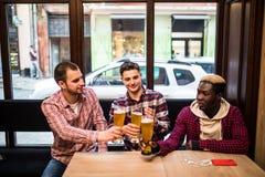 年轻愉快的多种族人朋友喝啤酒和谈话在客栈 库存照片