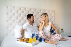 年轻愉快的夫妇吃早餐在床 图库摄影