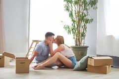 年轻愉快的夫妇在有移动的箱子的屋子里 库存图片