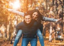 年轻愉快的夫妇在秋天获得乐趣在公园 库存照片