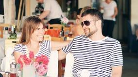 年轻愉快的夫妇在街道咖啡馆坐他们的假期 免版税库存图片