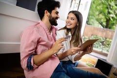 年轻愉快的夫妇坐地板与膝上型计算机预定的假日 库存图片
