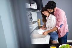 年轻愉快的夫妇是洗碗,当在家时做清洁 免版税库存图片