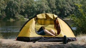 年轻愉快的夫妇进入的帐篷和去放松 r 他们有浪漫片刻 森林和河 股票录像