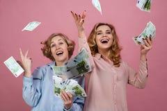 年轻愉快的女孩以欢欣投掷现金 他们享受成功和繁荣、金融市场和赢取的抽奖 库存照片