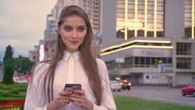 年轻愉快的女孩在市中心键入在她的智能手机的消息在日落在夏天,通信概念 股票录像