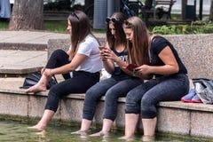 年轻愉快的女孩在水中的放松腿 免版税库存照片