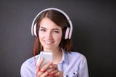 年轻愉快的女孩坐地板和听的音乐 免版税库存图片