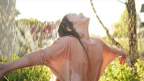 年轻愉快的女孩获得乐趣在雨下 微笑的湿孩子微笑和有心情户外 影视素材
