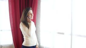 年轻愉快的女孩谈话在电话在窗口附近 影视素材