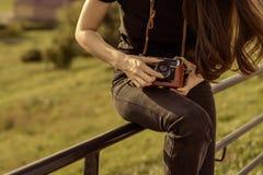 年轻愉快的女性摄影师在有减速火箭的照相机的公园走 库存照片