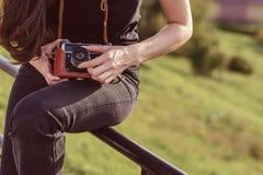 年轻愉快的女性摄影师在有减速火箭的照相机的公园走 图库摄影