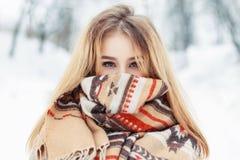 年轻愉快的妇女佩带的冬天布料 在面孔的围巾 免版税库存照片