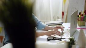 年轻愉快的妇女听音乐和工作由膝上型计算机 股票视频