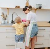年轻愉快的妇女在厨房洗着杯子和盘子 她的一点儿子帮助 免版税库存图片