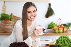 年轻愉快的妇女在厨房里拿着白色杯子并且看照相机,当坐在木桌上在中时 库存照片