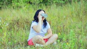 年轻愉快的妇女坐在清洁饮用的茶和赞赏的自然的草 影视素材