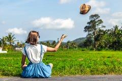 年轻愉快的妇女热带画象有草帽的在有可可椰子和热带树的一条路 巴厘岛 免版税库存图片