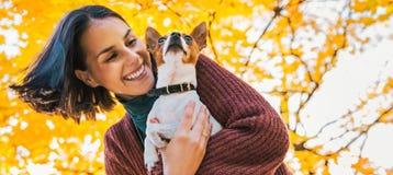 年轻愉快的妇女画象有小的逗人喜爱的狗的在公园 免版税库存照片