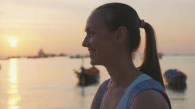 年轻愉快的妇女画象看照相机在慢动作的海滩 股票录像