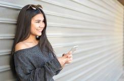 年轻愉快的妇女talikng和短信的消息与她的流动酸碱度 图库摄影