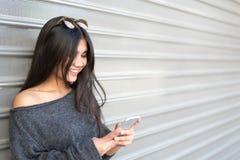 年轻愉快的妇女talikng和短信的消息与她的流动酸碱度 免版税库存照片