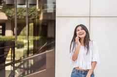 年轻愉快的妇女talikng和短信的消息与她的流动酸碱度 免版税库存图片