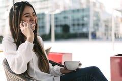 年轻愉快的妇女talikng和短信的消息与她的流动酸碱度 库存照片