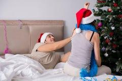 年轻愉快的家庭在床上的庆祝圣诞节 库存照片
