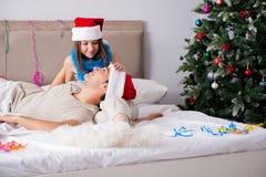 年轻愉快的家庭在床上的庆祝圣诞节 免版税库存图片