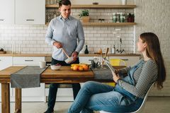 年轻愉快的已婚夫妇在厨房里 人支持厨房用桌,并且准备早餐孕妇坐 库存图片