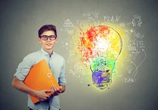 年轻愉快的微笑的人画象有橙色文件夹笔记本的在有一个明亮的电灯泡企业想法剪影的一个混凝土墙附近 免版税库存图片