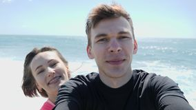 年轻愉快的微笑的夫妇记录的theirselves在多岩石的海滩的一个selfie方式下 强风和波浪 股票录像