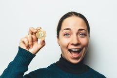 年轻愉快的微笑的女孩在手中显示cryptocurrency,新的真正金钱的金黄Bitcoin硬币-标志 图库摄影