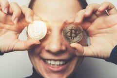 年轻愉快的微笑的女孩在手在她的眼睛前面- cryptocurrency,新的真正金钱的标志上拿着金黄Bitcoin硬币 免版税库存照片