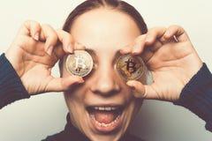 年轻愉快的微笑的女孩拿着金黄Bitcoin硬币- cryptocurrency,新的真正金钱的标志 免版税图库摄影