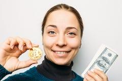 年轻愉快的微笑的女孩拿着金黄Bitcoin硬币- cryptocurrency,新的真正金钱的标志 库存照片