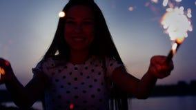 年轻愉快的微笑的妇女,跳舞与闪烁发光物在慢动作的日落,与烟花在海滩的日落 股票视频