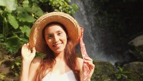 年轻愉快的微笑的混合的族种旅游女孩画象白色礼服和草帽的有使的狂放的密林瀑布惊奇 生活方式 股票视频