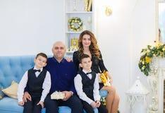 年轻愉快的母亲和父亲坐有儿子的沙发在装饰的屋子里为圣诞节假日 免版税库存照片