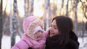 年轻愉快的母亲特写镜头有快乐的孩子的在冬天户外 桃红色连衫裤的女婴微笑在妈妈的手上的 股票录像