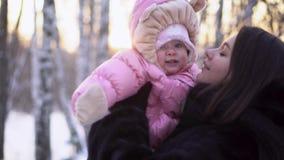 年轻愉快的母亲特写镜头有快乐的孩子的在冬天户外 桃红色连衫裤的女婴微笑在妈妈的手上的 影视素材