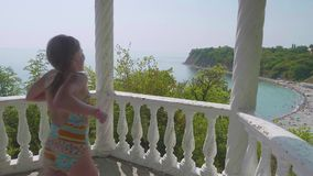 年轻愉快的白种人女孩跑由栏杆决定并且看下来海海滩 Slowmo 股票录像