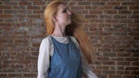 年轻愉快的白肤金发的女孩使用与头发,调情的人概念,砖背景 影视素材