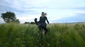 年轻愉快的白肤金发的女孩在一块绿色麦田跑在晚上以雨天空为背景 从的看法 股票录像